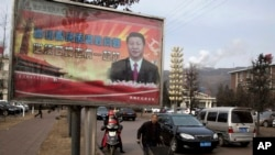 FILE - A billboard shows Chinese President Xi Jinping. Zhang said police were demanding that he cease his political writing and give up his column.