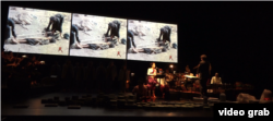 "Artists run through a dress rehearsal for ""Bangsokol: A Requiem for Cambodia"" at the Brooklyn Academy of Music in New York. Behind the performers archival footage plays. (Ye Yuan/VOA)"