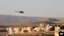This citizen journalist image provided by Shaam News Network purports to show a helicopter gunship flying a bombing run in al-Qalmoun, Syria, July 24, 2012.