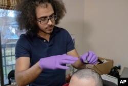 یوینورسٹی آف کیلی فورنیا کے انجنیئر ڈیوڈ موسز، رضاکار کے دماغ میں برقی تاریں نصب کر رہے ہیں۔