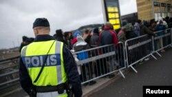 难民抵达瑞典,警察在旁观看(2015年11月19日)