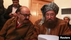 Maulana Sami ul-Haq (kanan), salah seorang juru runding Taliban dan Irfan Siddiqui, perwakilan dari emerintah Pakistan mendiskusikan pernyataan bersama sebelum menggelar konferensi pers di Islamabad, Pakistan, 6 Februari 2014 (Foto: dok).