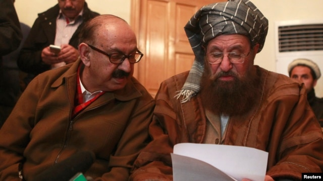 FILE- Maulana Sami ul-Haq (R), one of the Taliban negotiators, and Irfan Siddiqui, a government negotiator, discuss a joint statement before a news conference in Islamabad, Pakistan, Feb. 6, 2014.