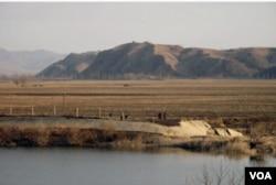 在田间劳作的朝鲜妇女以及山上的了望塔