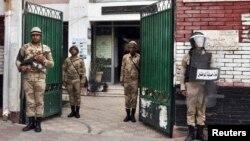 Polisi Mesir tengah berjaga di halaman sekolah yang digunakan sebagai salah satu TPS di Kairo, 13 Januari 2014 (Foto: dok). Lima orang polisi dilaporkan tewas ditembak orang-orang bertopeng dan bersenjata di sebuah pos pemerikasaan, provinsi Beni Suef, 100 ilometer dari Kairo (23/1).