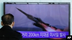 FILE - A South Korean man watches a TV news program showing file footage of a missile launch conducted by North Korea, in Seoul, South Korea, March 13, 2015.