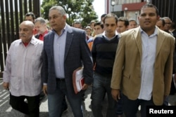 Pedro Carreno, second from left, deputy of Venezuela's United Socialist Party, arrives at the Supreme Court to challenge the swearing in of three opposition deputies, next to fellow deputies in Caracas, Jan. 7, 2016.