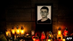 Candles and an image of investigative journalist Jan Kuciak are left outside Aktuality, the Slovakian news outlet where he worked. (Vladimir Simicek | AFP)