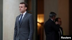 French President Emmanuel Macron accompanies a guest after a meeting at the Elysee Palace in Paris, Jan. 12, 2018.