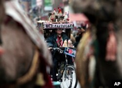 FILE - Luis Cajigas, 82, rides his tricycle decorated with religious and cultural symbols in the procession marking the 35th Anniversary of the Three Kings Parade in East Harlem, New York, Jan. 6, 2012.