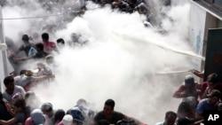 Cảnh sát Hy Lạp xịt hơi từ bình chữa lửa trong cố gắng giải tán hàng trăm người di cư tụ tập để làm thủ tục đăng ký tại sân vận động ở thị trấn Kos, ngày 11/8/2015.