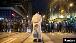 在香港坚尼地城,一名宗教人士站在防暴警察前。(2019年8月4日)