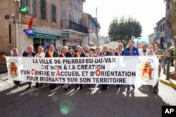"""Local residents hold a banner reading: """" City of Pierrefeu says no to the creation of a reception center for migrants"""" during a march in Pierrefeu, southeastern France, Oct. 8, 2016."""