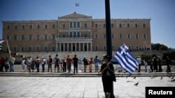 Seorang perempuan memegang bendera Yunani dan bendera Siprus yang berukuran lebih kecil di depan gedung parlemen Yunani di Athena, dalam aksi mogok Hari Buruh 2013 (May Day). Angkutan kapal feri dan kereta api di Yunani terhenti akibat aksi mogok ini (1/5).