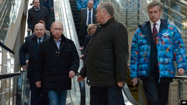 Russian President Vladimir Putin, foreground left, and Railways Chief Vladimir Yakunin, second right, visit the Olympic Park railway station at the Black Sea resort of Sochi, southern Russia, Jan. 4, 2014.