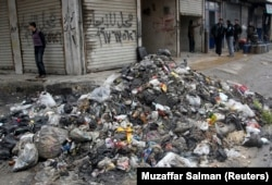 Men stand near garbage filling a street in Aleppo, February 11, 2013. Poor waste management and lack of hygiene have fuelled its spread