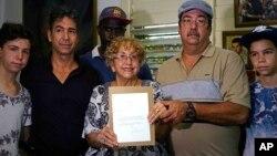 leana Yarza, de 76 años, rodeada de su familia, sonríe sosteniendo una copia impresa de una carta que el presidente Barack Obama le envió en el primer vuelo postal directo entre Estados Unidos y Cuba.