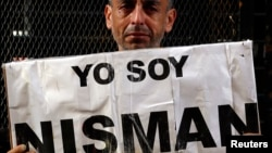 """Marcelo Novillo, whose son Adrian was a victim of a violent crime, cries as he holds up a sign that reads """"I am Nisman"""" outside the office of the prosecutor who is investigating the death of prosecutor Alberto Nisman in Buenos Aires, Jan. 22, 2015."""