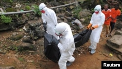 Health workers remove the body of a young man who local residents say died of Ebola in Monrovia, Liberia, Sept. 11, 2014.