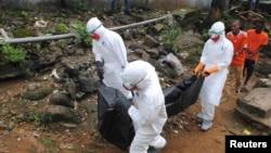 Petugas medis memindahkan jenazah seorang pria berusia 29 tahun yang menurut warga meninggal di Monrovia, Liberia (11/9). (Reuters/James Giahyue)