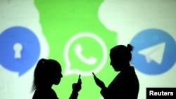 手机使用者站在加密通讯平台Telegram的标识前。加密通讯平台Telegram的标识是一只纸飞机。(2018年3月28日资料照片)
