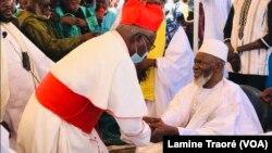 Le cardinal Philipe Ouédraogo, archevêque de Ouagadougou allant saluer l'iman après la prière de Ramadan, Ouagadougou, le 13 mai 2021. (VOA/Lamine Traoré)