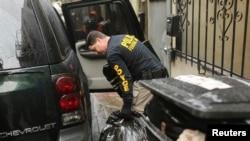 警方调查人员从旧金山中国城致公堂总堂取出大包东西。(2014年3月26日)