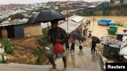 Rohingya refugees walks along the refugee camp during rain in Cox's Bazar, Bangladesh, July 25, 2018.