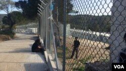 Along the chain-link fence at the camp in Lesbos, Greece, an occasional aid worker, local resident or journalist stops to talk to refugees inside, who are eager for any news, April 1, 2016. (H. Murdock/VOA)