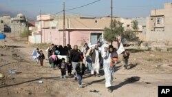 Người dân lánh chiến sự giữa quân đội Iraq và những kẻ chủ chiến Nhà nước Hồi giáo đi qua một ngõ ở quận Gogjali, ờ vùng ngoại ô phía đông Mosul, Iraq, ngày 5 tháng 10, 2016.