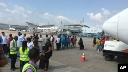 Des passagers passent à un contrôle avant de prendre un avion à l'aéroport d'Abuja, Nigeria, 15 octobre 2016.
