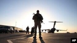 Binh sỹ đứng gác gần một máy bay quân sự ở Kandahar, Afghanistan, 8/12/2013.