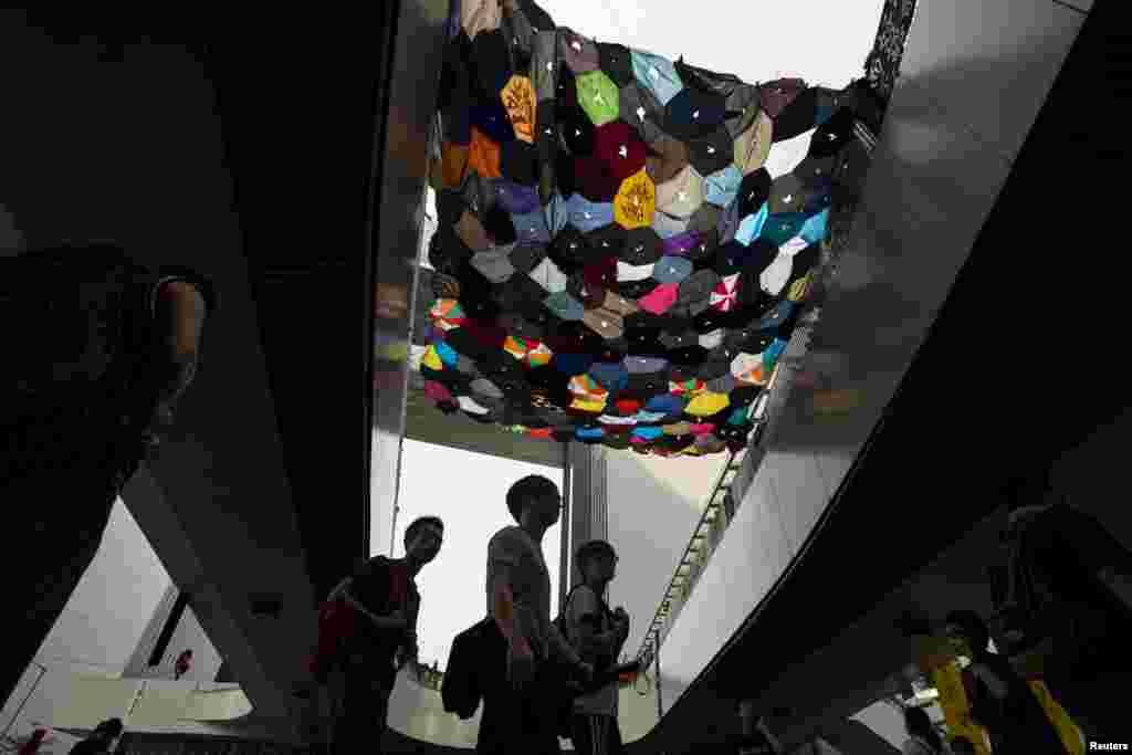 Protesters walk under an art installation made from umbrellas by a local artist outside the government headquarters in Hong Kong, Oct. 3, 2014.