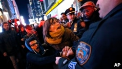 Police arrests protesters rallying against a grand jury's decision not to indict the police officer involved in the death of Eric Garner attempted to block traffic at the intersection of 42nd Street and Seventh Avenue near Times Square, Thursday, Dec. 4, 2014, in New York. (AP Photo/Jason DeCrow)