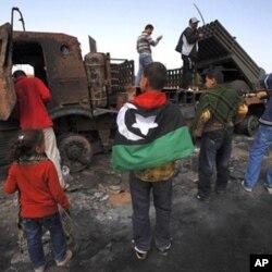 3月23日一群利比亚民众围观被联军炸毁的政府军的重武器