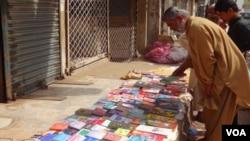 ایک خریدار اپنے پسند کی کتاب دیکھ رہاہے