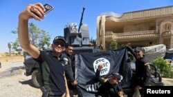 Members of the Iraqi Army are photographed with an Islamic State flag, claimed after fighting with Islamic State militants in western Mosul, Iraq, June 26, 2017.