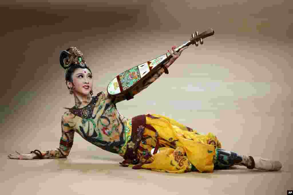 베이징에서 열린 중국패션주간 개막쇼에서 '네타이거(NE.TIGER) 2018 고급여성복 콜렉션'에 출연한 무용수가 전통 악기 비파를 들고 무대 위에서 연기하고 있다.
