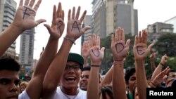 """Ủng hộ viên của nhà lãnh đạo đối lập Venezuela Henrique Capriles viết chữ """"gian lận"""" trong bàn tay trong khi biểu tình đòi kiểm lại phiếu"""