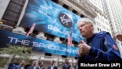 Sir Richard Branson, right, founder of Virgin Galactic, and company executives gather for photos outside the New York Stock Exchange before his company's IPO, Monday, Oct. 28, 2019.
