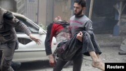 A resident carries an injured man through a site damaged from what activists said was an airstrike by forces loyal to Syria's President Bashar al-Assad on the main field hospital in the town of Douma, Syria, Oct. 29, 2015.