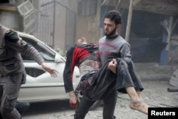 In the Syrian town of Douma, a resident carries an injured man past a damaged site, Oct. 29, 2015. Activists said Assad loyalists bombed a field hospital there.