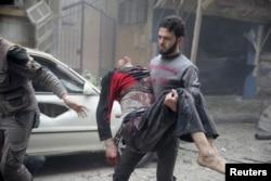 ຢູ່ໃນເມືອງ Douma ຂອງຊີເຣຍ ພົນລະເມືອງຄົນນຶ່ງ ອຸ້ມເອົາຊາຍຜູ້ໄດ້ຮັບບາດເຈັບ ຜ່ານອາຄານບ່ອນທີ່ໄດ້ຮັບຄວາມເສຍຫາຍ, ເຊິ່ງບັນດານັກເຄື່ອນໄຫວ ກ່າວວ່າ ພວກຈົງຮັກພັກດີ ທ່ານ Assad ໄດ້ຖິ້ມລະເບີດຖັງ ໃສ່ໂຮງໝໍພາກສະໜາມ ຢູ່ແຫ່ງນັ້ນ ເມື່ອວັນທີ 29 ຕຸລາ 2015.