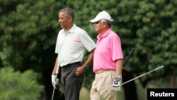 President Barack Obama and Malaysia's Prime Minister Najib Razak walk off 18th hole while playing a round of golf at the Clipper Golf course on Marine Corps Base Hawaii during Obama's Christmas holiday vacation in Kaneohe, Hawaii, December 24, 2014.