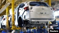 戴口罩的工人在武汉的东风集团本田汽车公司的一条生产线上工作。(2020年3月16日)
