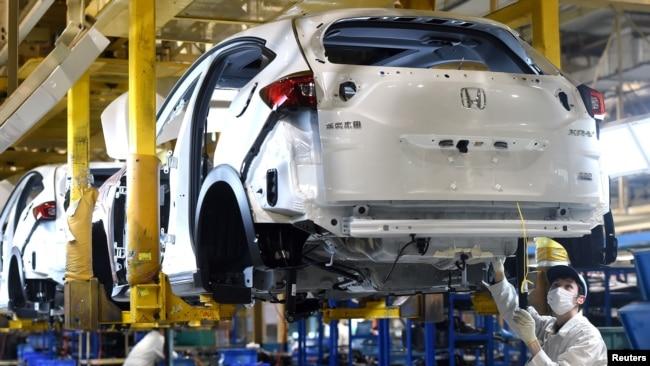 戴口罩的工人在武漢的東風集團本田汽車公司的一條生產線上工作。 (2020年3月16日)