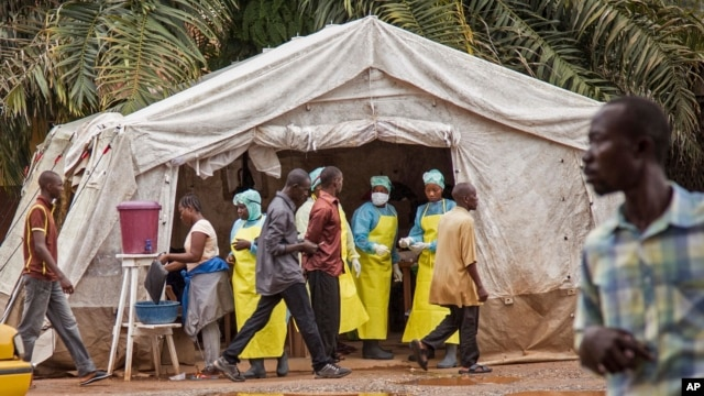 FILE - Health workers prescreen people for the deadly Ebola virus before they enter the Kenema Government Hospital in Kenema, Sierra Leone.