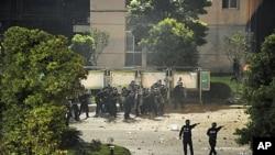 中国防暴警察9月17日在浙江晶科能源公司大门口用盾牌抵挡抗议者投掷的石块