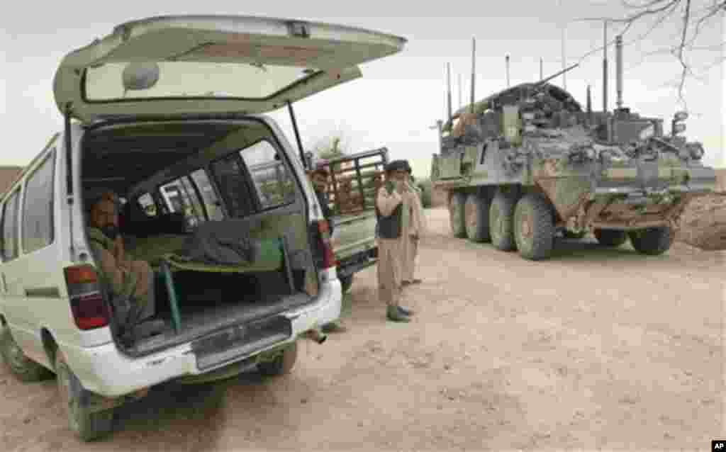 An armored military vehicle from the NATO-led International Security Assistance Force (ISAF) is seen at right, as the covered body of a person who was allegedly killed by a U.S. service member is seen inside a minibus in Panjwai, Kandahar province south o