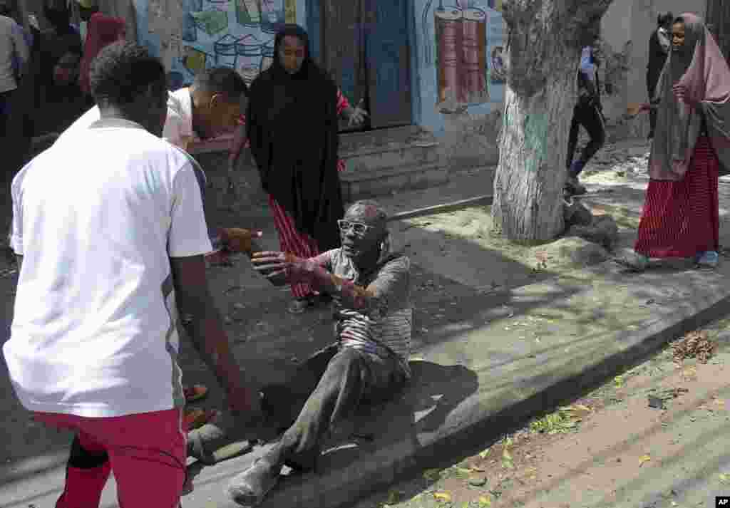 A wounded man reaches out to rescuers after a car bomb attack in Mogadishu, Somalia. A suicide car bomber detonated near the Weheliye hotel in the capital, killing a number of people on the busy Maka Almukarramah road, police said.